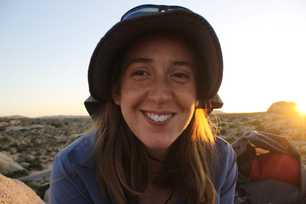 picture of sam in the joshua tree desert at sunset, in a hat, smiling